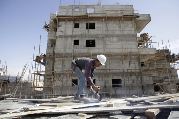 A Palestinian labourer works on a construction site in a Jewish settlement near Jerusalem known to Israelis as Har Homa and to Palestinians as Jabal Abu Ghneim November 16, 2011. Israel said on Tuesday it will invite bids soon for constructing 814 homes in occupied land it considers part of Jerusalem, pursuing a decision to speed up building in settlements after Palestinians won full membership in the U.N. cultural agency. REUTERS/Ammar Awad