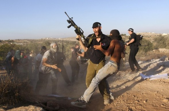 Jewish settlers dressed as Palestinian protesters clash with a settler during a drill in the West Bank settlement of Kiryat Arba.
