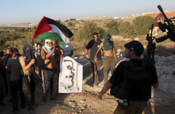 A Jewish settler stands guard as settlers dressed as Palestinian protesters participate in a drill in the West Bank settlement of Kiryat Arba.