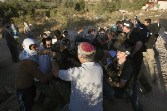 Jewish settlers dressed as Palestinian protesters clash with settlers during a drill in the West Bank settlement of Kiryat Arba