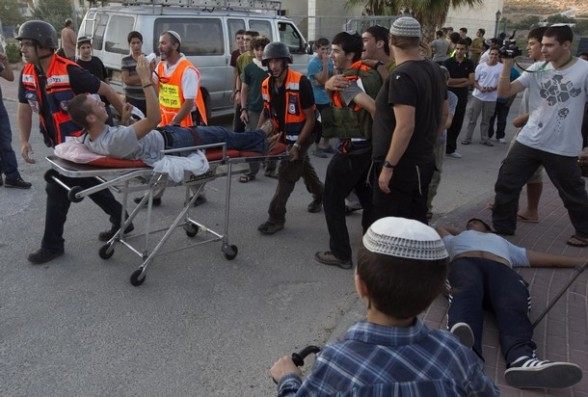 A Jewish settler playing the role of an injured person is wheeled on a stretcher during a drill in the West Bank settlement of Kiryat Arba.