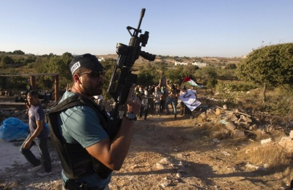 A Jewish settler stands guard as settlers dressed as Palestinian protesters participate in a drill in the West Bank settlement of Kiryat Arba
