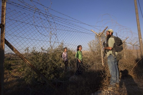 A Jewish settler participating in a drill speaks to girls through a fence in the West Bank settlement of Kiryat Arba