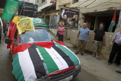 A car decorated with Palestinian flags and those from Palestinian parties and movements is driven around the Palestinian Shatila refugee camp in Beirut