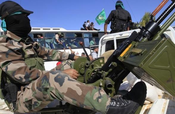 Hamas security men keep watch as a bus c