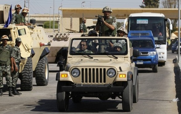 Soldiers from the Egyptian army escort a bus carrying Palestinian prisoners released from Israel, as part of a prisoners exchange deal, outside the Egyptian Rafah crossing
