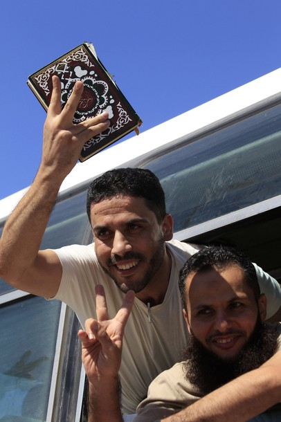 A released Palestinian prisoner holds a copy of the Koran as another flash the victory sign from a bus as they make their way through the Rafah border crossing between Egypt and Gaza
