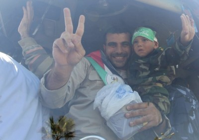 A Palestinian prisoner gestures as he holds his son after arriving at the Rafah crossing