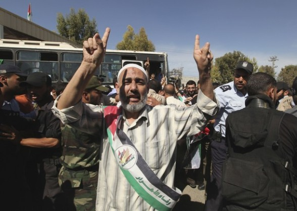 A Palestinian prisoner gestures after arriving to the Rafah crossing with Egypt in the southern Gaza Strip