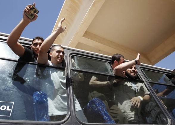 Palestinian prisoners, released by Israel in exchange for Israeli soldier Shalit, wave from buses as they make their way through the Rafah border crossing between Egypt and Gaza