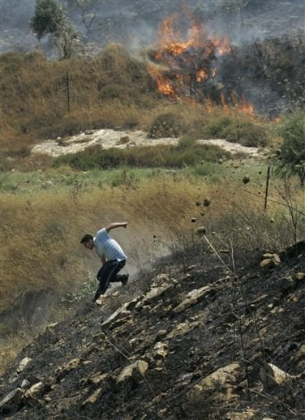 A Palestinian scrambles down a burnt hillside as he and others try to extinguish fires at an olive tree grove that they claimed was set ablaze by Israeli settlers, which could not be independently verified, in the northern West Bank village of Burin, near Nablus, Thursday, June 30, 2011. (AP Photo/Nasser Ishtayeh)