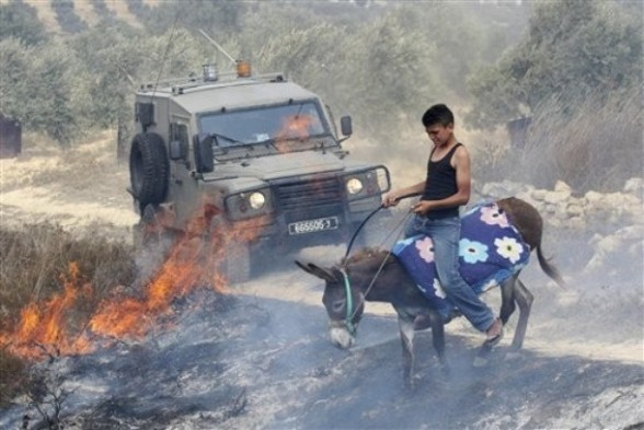 A Palestinian rides his donkey through a burning field as an Israeli army jeep drives by, after arsonists set fire to an olive grove in the West Bank village of Burin, near Nablus, Monday, Sept. 5, 2011. Palestinian witnesses say Jewish settlers set fire to an olive grove in a West Bank village Monday, after a mosque was torched allegedly by Jewish settlers in another West Bank village earlier. Both incidents occurred after the Israeli military razed three buildings in an unauthorized West Bank Jewish settlement outpost before dawn, and clashed with defiant settlers who reject a Supreme Court ruling ordering the enclave to be dismantled. (AP Photo/Nasser Ishtayeh)