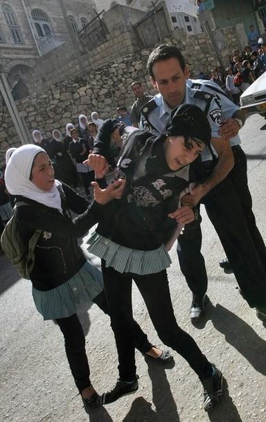 An Israeli policeman pulls away a Palest