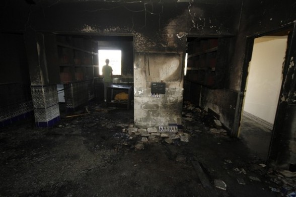A resident stands inside a burnt mosque in the Bedouin village of Tuba Zangaria