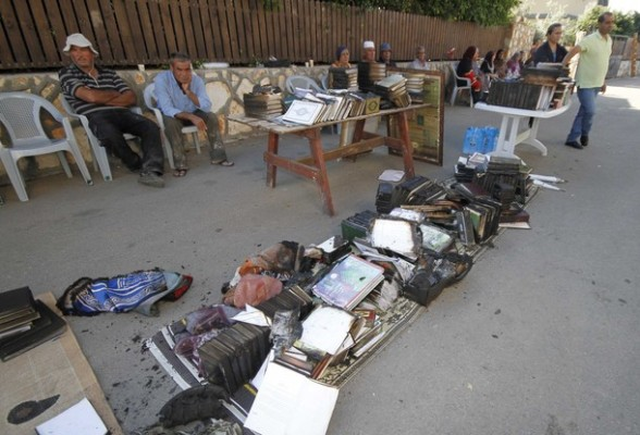 Residents sit next to damaged books outside a burnt mosque in the Bedouin village of Tuba Zangaria