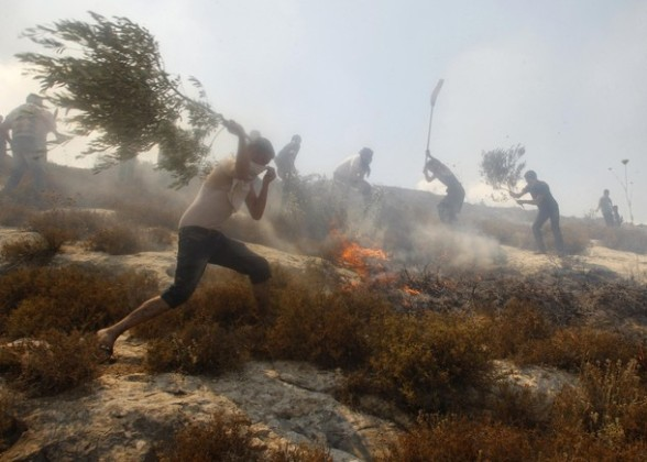 Palestinian villagers and firefighters try to extinguish a fire, they say was started by Jewish settlers, in a field in the West Bank village of Burin near Nablus June 30, 2011. Scorched hillsides and charred olive groves near Nablus pinpoint the latest acts of arson by hardline Jewish settlers against Palestinians who say they are ever more the victims of such attacks in the West Bank. Picture taken June 30, 2011.  To match feature PALESTINIANS-ISRAEL/SETTLERS  REUTERS/Abed Omar Qusini