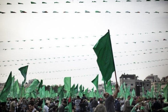 A Palestinian man waves a green Hamas party flag as tens of thousands of supporters of the Islamist movement gather in Gaza City to celebrate the 24th anniversary of its founding.  AFP PHOTO/MARCO LONGARI
