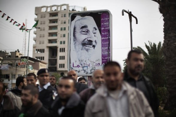 Palestinians gather near a poster of late Hamas spiritual leader Sheikh Ahmed Yassin during celebrations for the 24th anniversary of the foundation of the Islamist movement in Gaza City on December 14, 2011. AFP PHOTO/MARCO LONGARI