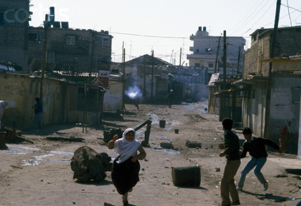 10 Feb 1988, Gaza, Gaza Strip --- Civilians flee gunfire from armed soldiers in the streets of Gaza. Violence broke out after rebel Israeli and Palestinian fighters protested in the occupied territory of Gaza during the first Intifada. --- Image by Patrick Robert/Sygma/CORBIS