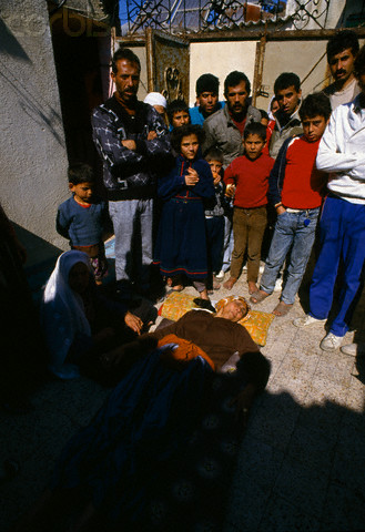 10 Feb 1988, Gaza, Gaza Strip --- A civilian woman lies wounded on the ground, surrounded by relatives. She was one of the victims of violence after rebel Israeli and Palestinian fighters protested in the occupied territory of Gaza during the first Intifada. --- Image by Patrick Robert/Sygma/CORBIS