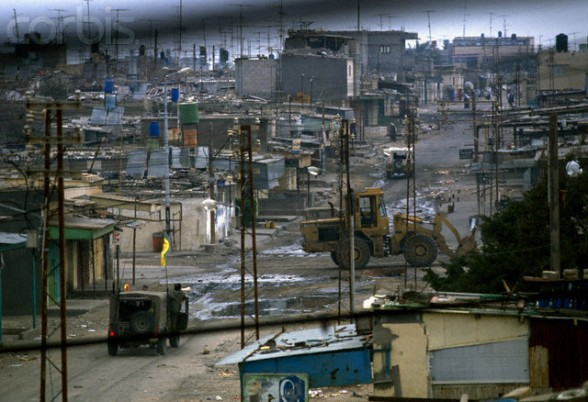 13 Feb 1988, Gaza, Gaza Strip --- Armed soldiers patrol the deserted streets of Gaza in military vehicles to impose a curfew. Violence broke out after rebel Israeli and Palestinian fighters protested in the occupied territory of Gaza during the first Intifada. --- Image by Patrick Robert/Sygma/CORBIS