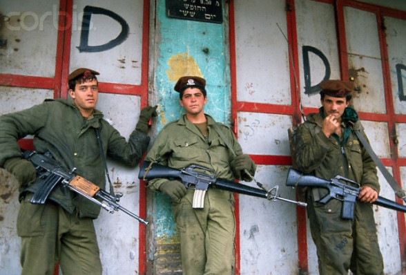 13 Feb 1988, Gaza, Gaza Strip --- Three armed soldiers patrol the streets of Gaza to impose a curfew. Violence broke out after rebel Israeli and Palestinian fighters protested in the occupied territory of Gaza during the first Intifada. --- Image by Patrick Robert/Sygma/CORBIS