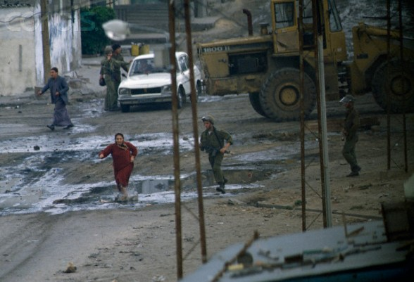 13 Feb 1988, Gaza, Gaza Strip --- A civilian Palestinian woman flees from armed soldiers in the streets of Gaza. Violence broke out after rebel Israeli and Palestinian fighters protested in the occupied territory of Gaza during the first Intifada. --- Image by Patrick Robert/Sygma/CORBIS