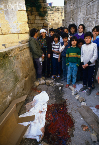 20 Feb 1988, Ramallah, West Bank --- Young mourners gather for a funeral near the bloody ground where a Palestinian civilian died during the uprising in Ramallah. Violence broke out after rebel Israeli and Palestinian fighters protested in the disputed territory of West Bank during the first Intifada. --- Image by Patrick Robert/Sygma/CORBIS