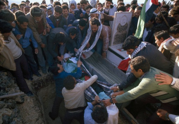 20 Feb 1988, Ramallah, West Bank --- During a funeral, mourners carrying Palestinian Liberation Organization flags protest the death of a Palestinian killed during the uprising in Ramallah. Violence broke out after rebel Israeli and Palestinian fighters protested in the disputed territory of West Bank during the first Intifada. --- Image by Patrick Robert/Sygma/CORBIS