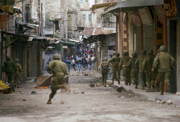 19 Feb 1988, Nablus, West Bank --- Soldiers face off against Palestinian demonstrators during a protest in the streets of Nablus after the Friday Prayer. Violence broke out after rebel Israeli and Palestinian fighters protested in the disputed territory of West Bank during the first Intifada. --- Image by Patrick Robert/Sygma/CORBIS