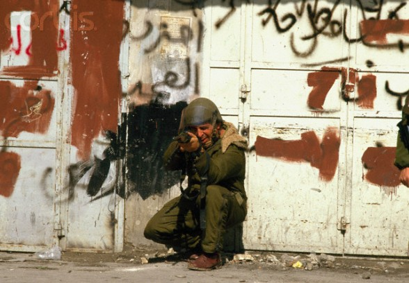 19 Feb 1988, Nablus, West Bank --- A soldier aims his assault rifle at Palestinian demonstrators during a protest in the streets of Nablus after the Friday Prayer. Violence broke out after rebel Israeli and Palestinian fighters protested in the disputed territory of West Bank during the first Intifada. --- Image by Patrick Robert/Sygma/CORBIS