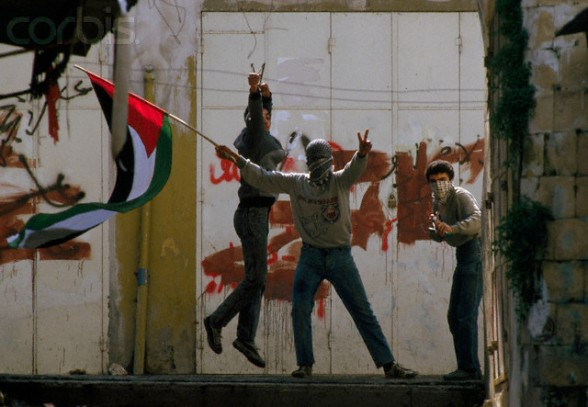 19 Feb 1988, Nablus, West Bank --- Demonstrators waving Palestinian Liberation Organization flags protest in the streets of Nablus after the Friday Prayer. Violence broke out after rebel Israeli and Palestinian fighters protested in the disputed territory of West Bank during the first Intifada. --- Image by Patrick Robert/Sygma/Corbis