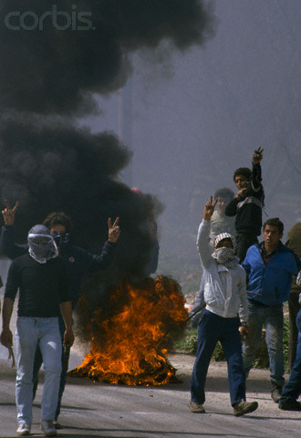 24 Feb 1988, Beit Ummar, West Bank --- While fires burn in the streets of Beit Omar, Palestinian demonstrators give peace signs during an uprising. Violence broke out after rebel Israeli and Palestinian fighters protested in the disputed territory of West Bank during the first Intifada. | Location: Beit Omar, West Bank.  --- Image by Patrick Robert/Sygma/CORBIS