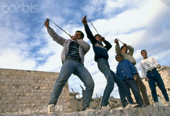 24 Feb 1988, Beit Ummar, West Bank --- Palestinian demonstrators throw stones at Israeli soldiers during a protest in the streets of Beit Omar. Violence broke out after rebel Israeli and Palestinian fighters protested in the disputed territory of West Bank during the first Intifada. | Location: Beit Omar, West Bank.  --- Image by Patrick Robert/Sygma/CORBIS