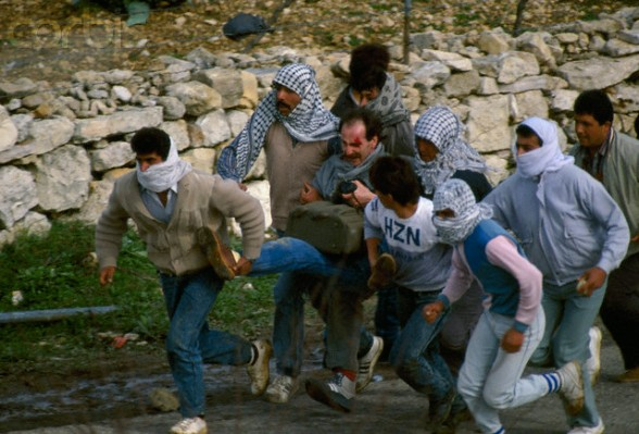 24 Feb 1988, Beit Ummar, West Bank --- Palestinian rebels carry a wounded photographer away from danger during a protest in the streets of Beit Omar. Violence broke out after rebel Israeli and Palestinian fighters protested in the disputed territory of West Bank during the first Intifada. | Location: Beit Omar, West Bank.  --- Image by Patrick Robert/Sygma/CORBIS