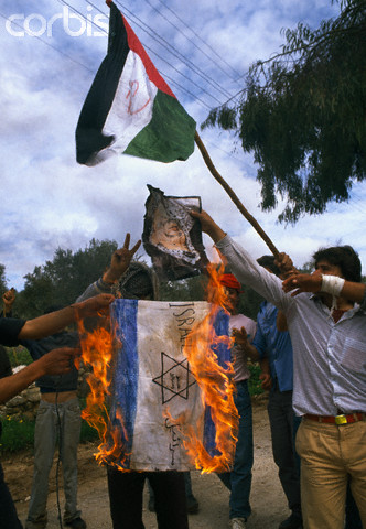 February 1988, West Bank --- Palestinian demonstrators burn the Israeli flag and wave the Palestinian Liberation Organization flag, outlawed by Israel, during an uprising. Violence broke out after rebel Israeli and Palestinian fighters protested in the disputed territory of West Bank during the first Intifada. --- Image by  Patrick Robert/Sygma/CORBIS