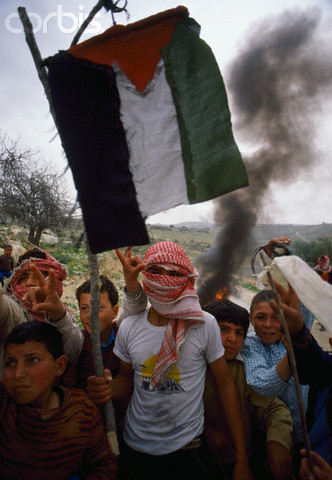 February 1988, West Bank --- Young Palestinian demonstrators wave Palestinian Liberation Organization flags, outlawed by Israel, during an uprising. Violence broke out after rebel Israeli and Palestinian fighters protested in the disputed territory of West Bank during the first Intifada. --- Image by  Patrick Robert/Sygma/CORBIS