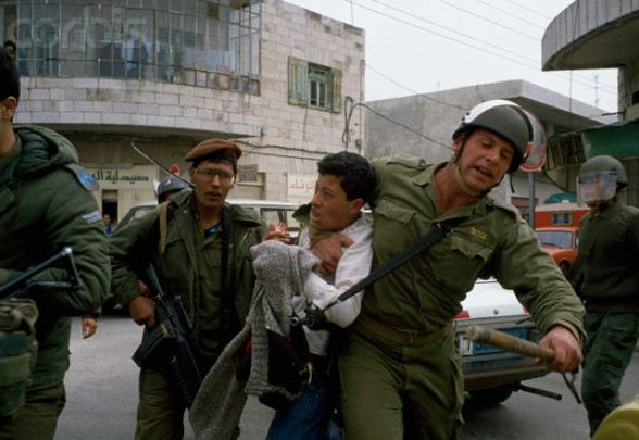 February 1988, West Bank --- Soldiers arrest a Palestinian demonstrator during an uprising. Violence broke out after rebel Israeli and Palestinian fighters protested in the disputed territory of West Bank during the first Intifada. --- Image by  Patrick Robert/Sygma/CORBIS
