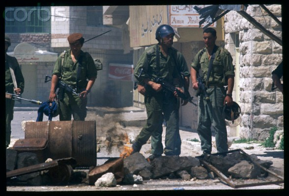 03 Apr 1988, Al-Bireh, West Bank --- Israeli soldiers confront a smoldering barricade while on patrol in the town of Al Birah during the Intifada. | Location: Al Birah, West Bank.  --- Image by  Bernard Bisson/Sygma/Corbis