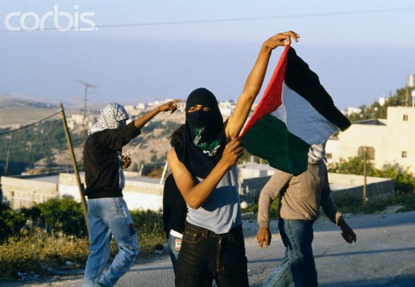 22 May 1990, Shu'fat, East Jerusalem, West Bank --- A masked Palestinian man holds up a Palestinian flag during a riot in Shufat, Jerusalem. The riot is in response to a shooting by a discharged Israeli soldier that occurred two days before in Rishon le-Ziyyon, which killed eight Palestinian laborers and wounded nine others. --- Image by Patrick Robert/Sygma/Corbis