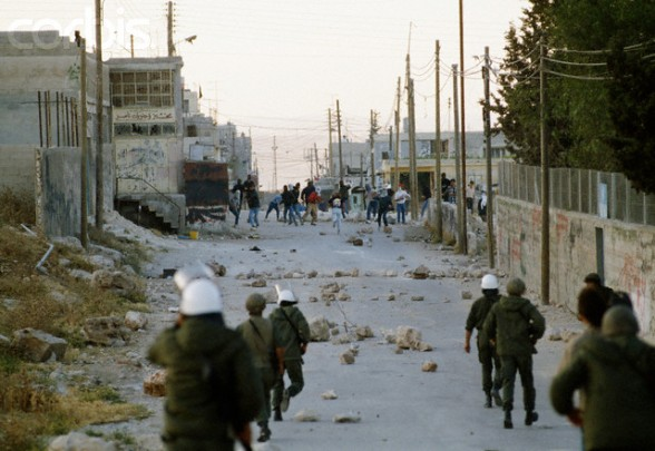 22 May 1990, Shu'fat, East Jerusalem, West Bank --- Israeli soldiers approach a group of rioting Palestinians in Shufat, Jerusalem. The riot is in response to a shooting by a discharged Israeli soldier that occurred two days before in Rishon le-Ziyyon, which killed eight Palestinian laborers and wounded nine others. --- Image by Patrick Robert/Sygma/Corbis