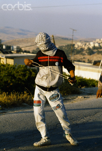 22 May 1990, Shu'fat, East Jerusalem, West Bank --- A masked Palestinian man carries a sling used to fling rocks during a riot in Shufat, Jerusalem. The riot is in response to a shooting by a discharged Israeli soldier that occurred two days before in Rishon le-Ziyyon, which killed eight Palestinian laborers and wounded nine others. --- Image by Patrick Robert/Sygma/Corbis