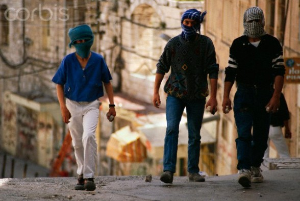 April 1989, Bethlehem, West Bank --- Masked  young men of the Intifada carry stones with them in preparation for a riot in Bethlehem. --- Image by Ricki Rosen/CORBIS SABA
