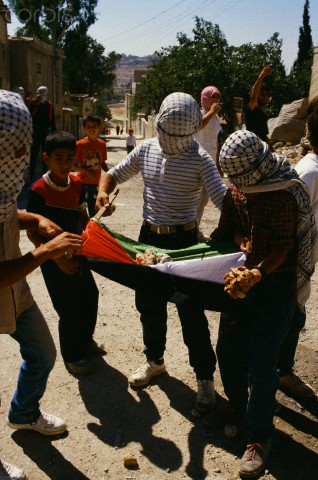 ca. 1989, Israel --- Masked children of the Intifada cradle rocks on a Palestine flag in preparation for a demonstration in the Kalandia Refugee Camp in the West Bank. | Location: Near Jerusalem, Israel.  --- Image by Ricki Rosen/CORBIS SABA