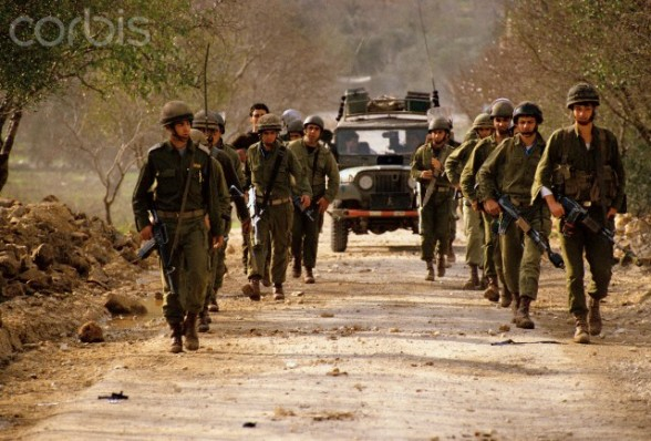 January 1988, West Bank --- Government soldiers patrol a road on the West Bank during the Intifada. --- Image by  Ricki Rosen/CORBIS SABA