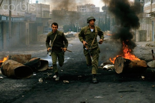 20 Jan 1988, West Bank --- Burning trash cans litter a village street in West Bank as Army soldiers run for cover during a riot in the Intifada. --- Image by Ricki Rosen/CORBIS SABA