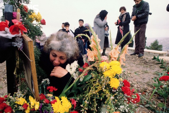 25 Dec 1988, Jerusalem, Israel --- A Palestinian family visits the grave of 15-year-old Nidel, who was killed in the Intifada, a violent uprising by Palestinians against the Israeli occupation. --- Image by Ricki Rosen/CORBIS SABA