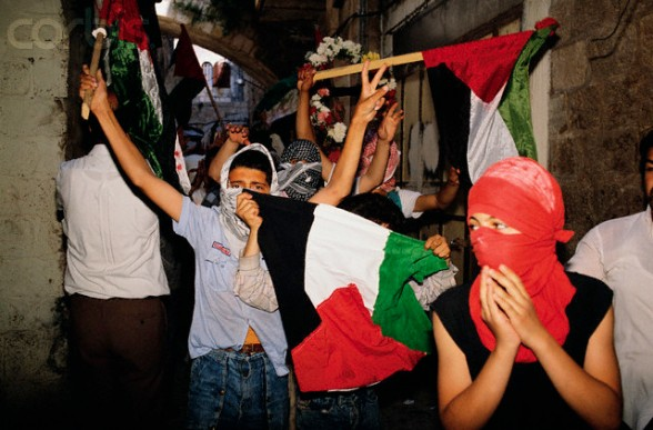11 Apr 1989, Jerusalem, Israel --- Masked Palestinians wave flags at a funeral for a slain Palestinian who was killed during the unrest. --- Image by Ricki Rosen/CORBIS SABA