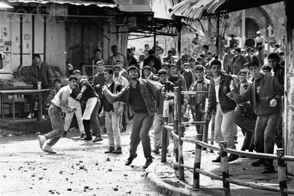 ca. 1988 - 1992, Khan Yunis, Gaza Strip --- A group of young Palestinian men hurl stones at Israeli soldiers in the town of Khan Yunis in the Gaza Strip. --- Image by David H. Wells/CORBIS
