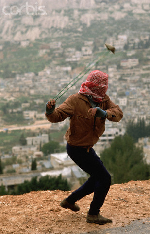 ca. 1988, Nablus, West Bank --- Palestinian Slinging a Rock --- Image by Peter Turnley/CORBIS